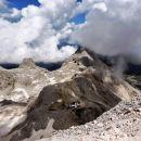 Kredarica in v ozadju Staničev dom pod Rjavino v oblakih
