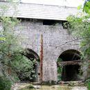 Po v strmi v levo pobočje Idrijce vsekani cesti nadaljujemo do klavž, pregrade, zgrajene d